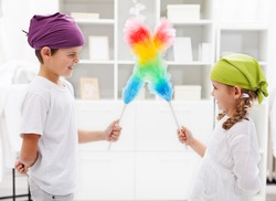 One for all and all for a tidy room - kids with duster brushes, focus on the girl