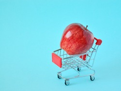 One fresh apple in small supermarket pushcart closeup.one red apple in a small shopping cart with on a yellow background. The concept of home delivery, online shopping, clearance sale.