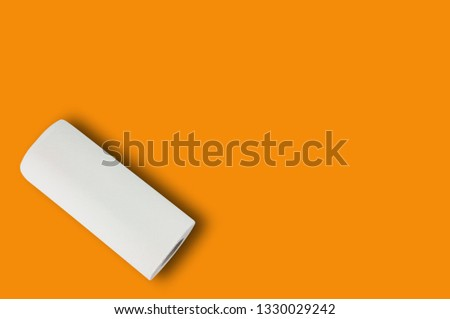 One full roll of white soft paper towel or paper for toilet on orange table with copy space for your text. Top view