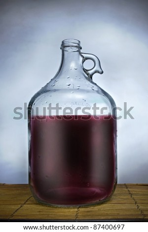 One gallon glass jug filled with wine, set on a table with blue background