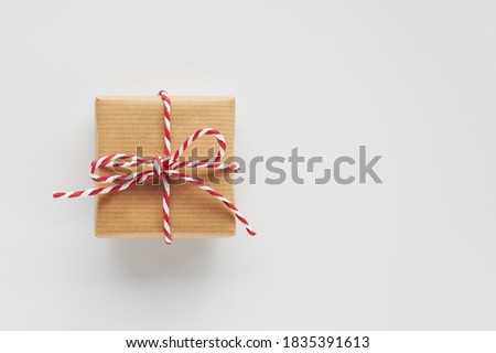 Photo of  One gift box wrapped in craft paper with striped baker's twine bow on white background. Top view, flat lay, copy space.