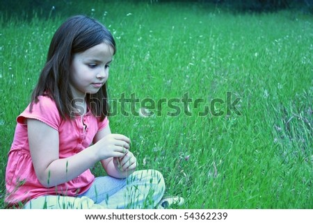 One girl about to blow on dandelion