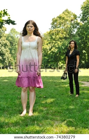 One girl is offended and her friend is calling for her - outdoors in park