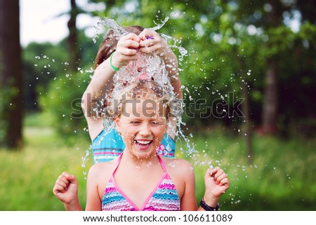 one girl splashing a water balloon to another girl