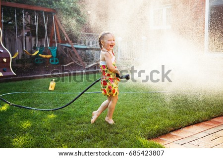 One girl splashing with gardening house on backyard on summer day. Child playing with water outside at sunset. Candid moment, lifestyle home kid activity.