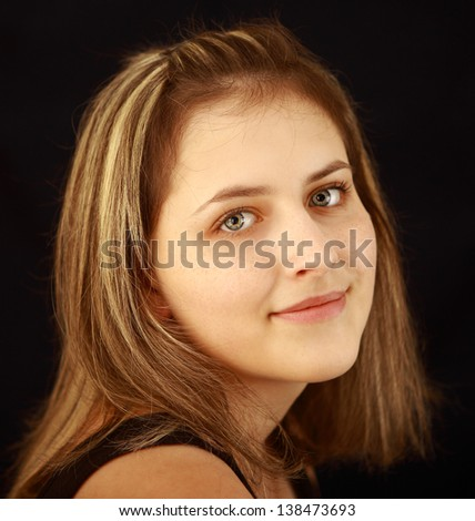 One girl teenager, aged 17, a natural beauty, smile, freckles on his face, gray eyes, brown hair with highlights, close-up portrait on black background.