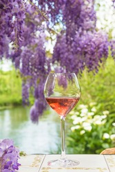 One glass of pink wine on the table outdoors with blooming purple wisteria near the river. Close up, selective focus