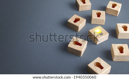 One glowing light bulb idea among many dark off. Concept choosing best suitable idea from presented. Developing startup. Business accelerator. Innovation promising technologies. Search for talent. Stock photo ©