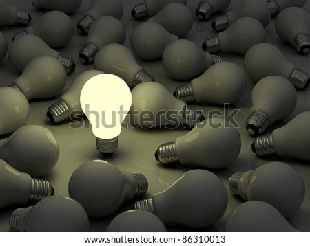 One glowing light bulb standing out from the unlit incandescent bulbs