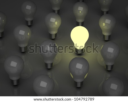 One glowing light bulb standing out from the unlit incandescent bulbs, the different concept