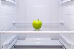 one green Apple on a shelf in an empty refrigerator