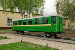 One green carriage of passenger train on pedestal, railway transport monument. Small size narrow-gauge wagon of old Soviet epoch. Railroad transporting scenery