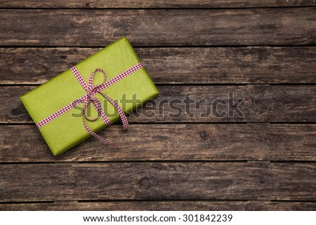 One green gift box wrapped in apple green box with red white checked ribbon on old rustic wooden brown background for christmas.