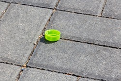 One green plastic cork from lemonade or mineral water on gray paving stones. Urban pollution