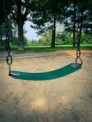 One green swing in a children's playground. Groomed sand on the ground with pine trees in the background on a bright summer day.