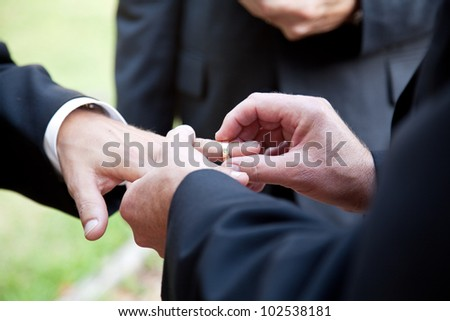 ... One groom placing the ring on another man's finger during gay wedding.