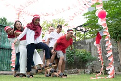 one group of participants tried to step together during a traditional bakiak competition on Indonesia's Independence Day celebration in the field with balloons and small red and white decorations