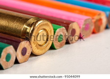One gun bullet together with colorful pencils packed in a row