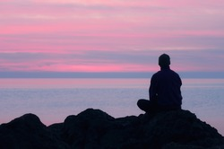 One guy sits on a rock by the sea and looking at pink sunset