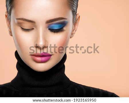One half face of a beautiful white woman with  bright makeup and the other is natural. Woman portrait with a deep blue eye makeup of one eye. Natural and  vivid make-up on a female face. Fashion style Foto stock ©