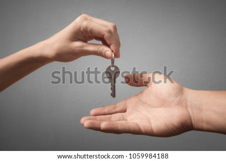 One hand giving key to another on isolated background. Process of buying renting selling. Agreement between two people for sales, and purchase.