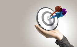 One hand holding a target with three darts hitting the center, beige background. Illustration of control and effective business solutions.