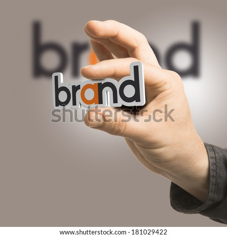 One hand holding the word brand over a beige background. Branding concept. The image is a composition between 2D illustration, 3D rendering and photography
