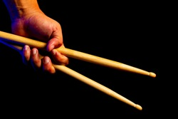 one hand holding wooden drum stick on fist with dark background, red and blue rim light, musician concept