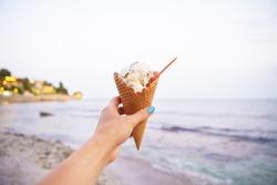 one hand holds tasty ice cream on a summer beach.