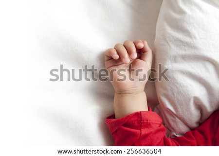 One hand of a sleeping baby girl, on a white bed sheet and blanket, beside a white pillow, making a fist, closeup