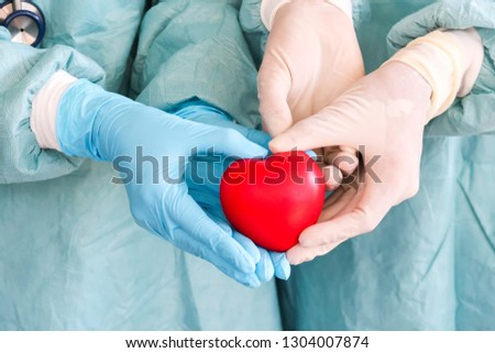 One hand of many doctors holding a red heart balloon, heart health care, loved ones #1304007874