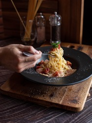 one hand use fork scoop spaghetti in black plate