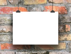 One hanged horizontal paper sheet frame with clips on weathered brick wall background