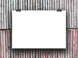 One hanged horizontal paper sheet with clips on vertical clay tiles wall background