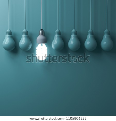 One hanging eco energy saving light bulb glowing and standing out from unlit incandescent bulbs on green pastel color wall background , leadership and different creative idea concepts . 3D rendering.