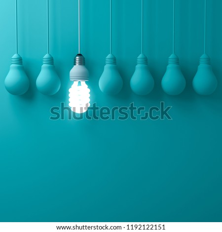 One hanging eco energy saving light bulb glowing and standing out from unlit incandescent bulbs on dark green pastel color wall background leadership and different creative idea concepts 3D rendering