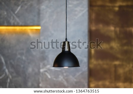 One hanging lamp hangs in the room with gray walls. Horizontal photography