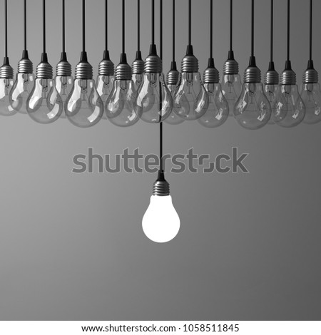 One hanging light bulb glowing different and standing out from unlit incandescent bulbs on dark grey background , leadership and different business creative idea concept. 3D rendering.