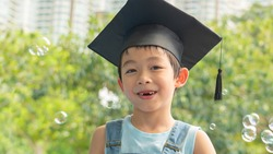 One happy and cute boy with the graduation cap/hat on is closing his eyes and smiling with fun at the park. The lovely kid and the front milk teeth missing at outdoor play area.