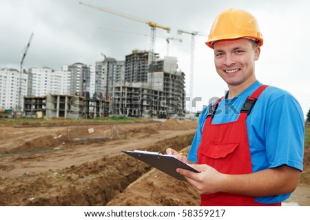 One happy builder worker with clipboard inspecting works at construction site