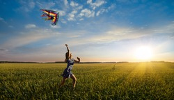 one happy little girl running on field with kite