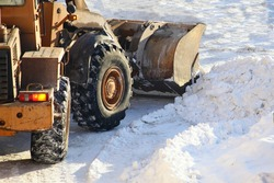 One heavy wheeled articulated tractor removes a snow with scraper shovel blade snowplow on highway road after heavy snowfall at Sunny winter day, top front view close-up