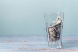 One hundred banknote rolled up in the glass on a wooden table and a blue background. Copy space, saving money concept