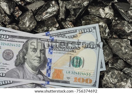 One hundred dollar banknotes on coal mine close up. Mining industry concept with dollars and coal