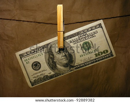One hundred dollar bill hanging on a clothes pin