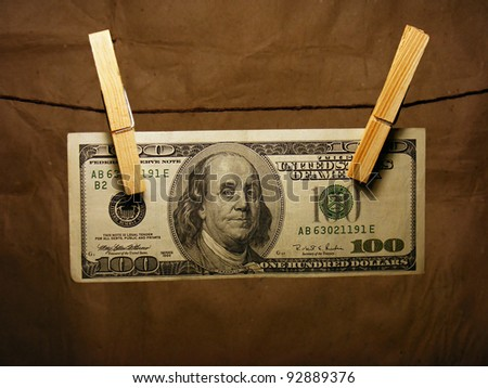 One hundred dollar bill hanging on a clothes pins