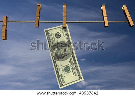 One hundred dollar bill hanging on a clothesline in front of a cloudy sky