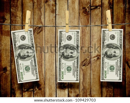 One hundred dollar bills hang on pins over wood background