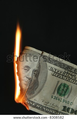 One hundred dollars bill on fire over black background - stock photo