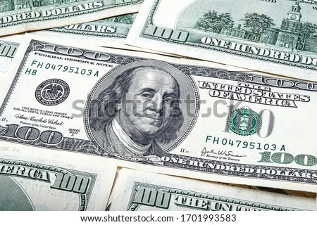 One hundred dollars. Portrait of President Benjamin Franklin. US dollars background. Closeup of a lot of banknotes hundred dollar bills. American currency.